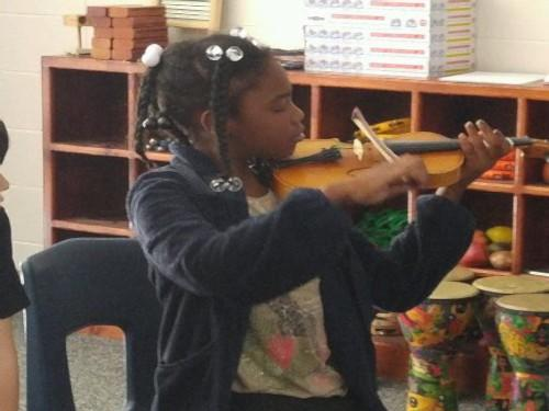 A 4th grader gives her hand a try at the violin!