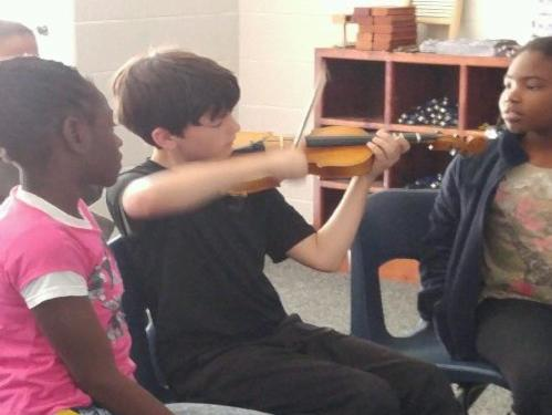 4th graders patiently wait for their turn to try the violin.
