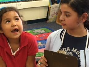 6th grader reading to a kinder student