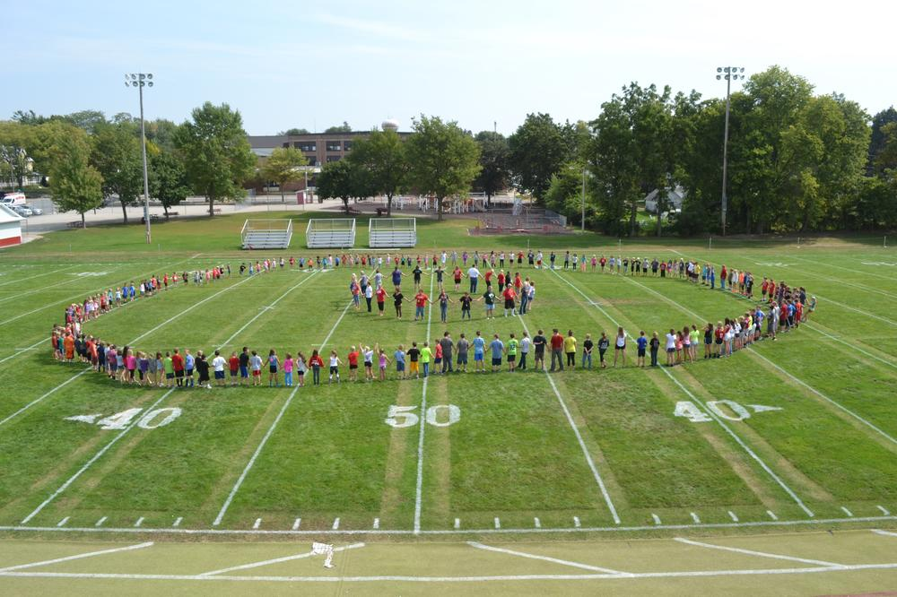 Elementary students and teachers in a circle on the football field