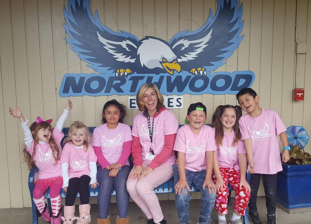 students and teacher in pink Northwood logo t-shirt in front of Northwood Eagles sign