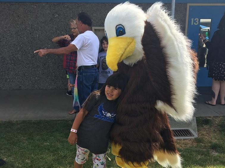 principal knox in an eagle mascot costume with student