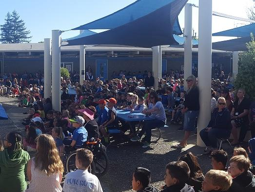 Parents and Students Attending Our Annual Talent Show! parents and students  sitting at lunch tables outside
