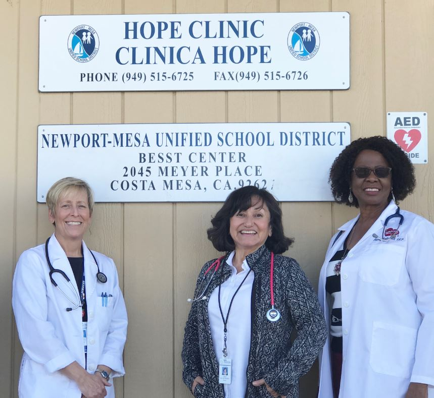 Three school nurses in front of clinic