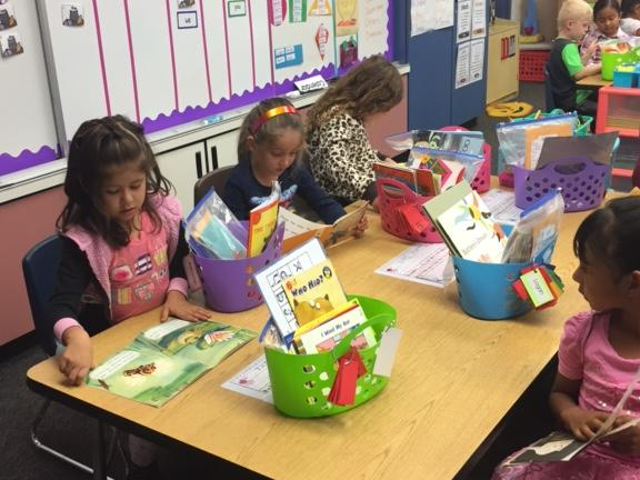 Students reading at a table in a classroom