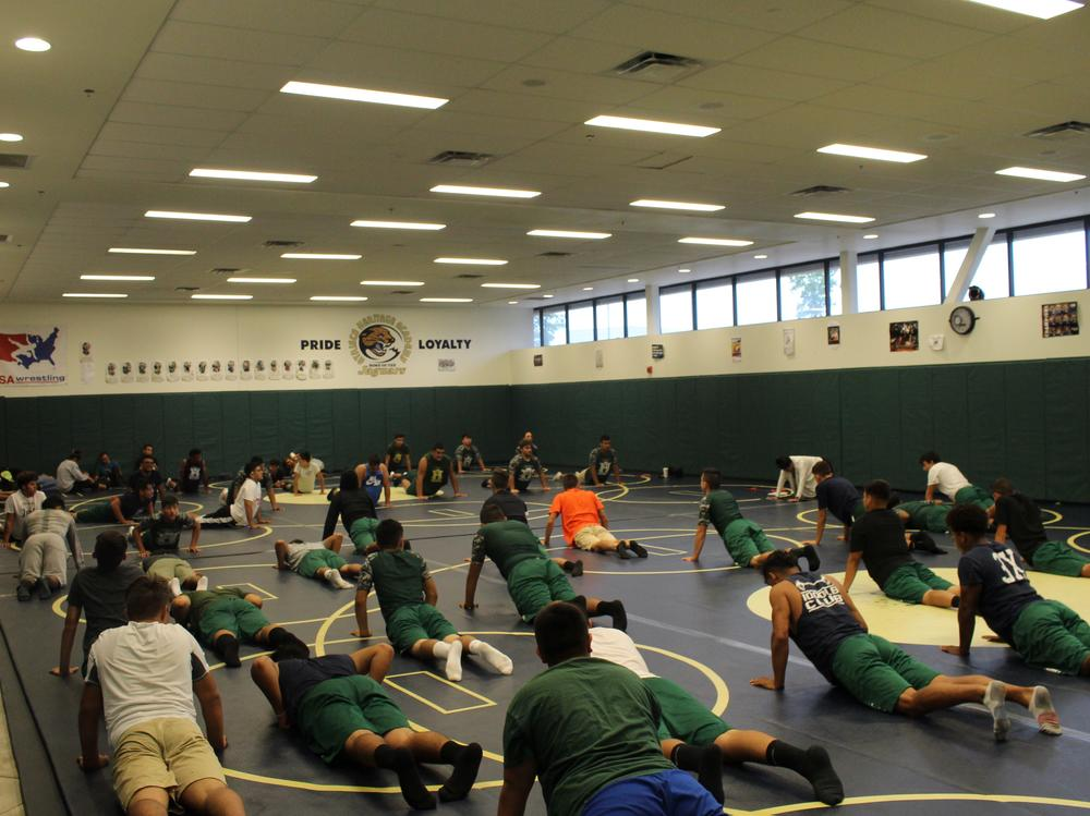Football team performs yoga after a hard fought game.