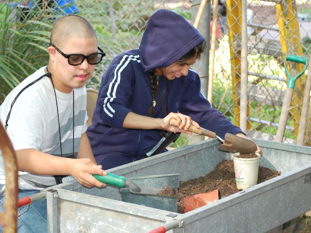 Two Students Planting in Garden