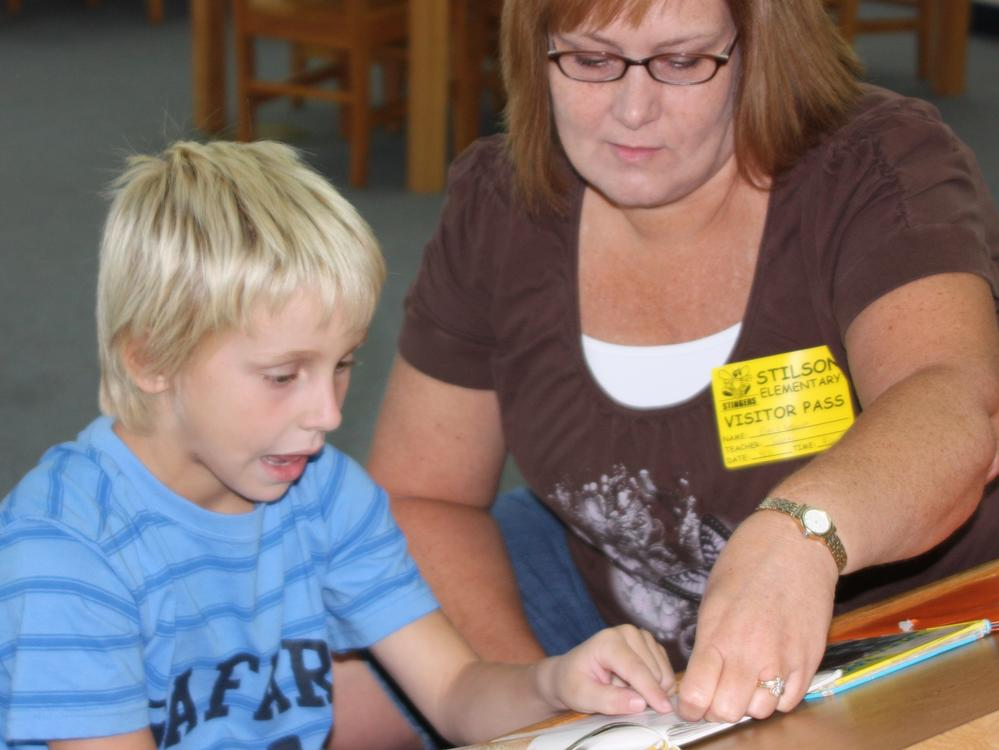 Parent volunteer reads to a child