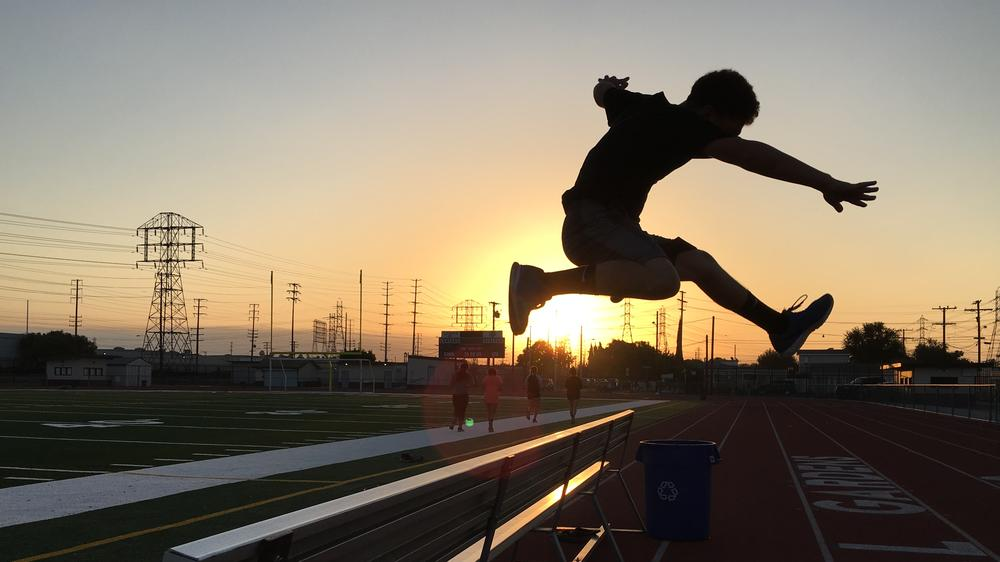 Student jumping over bench in front of a sunrise