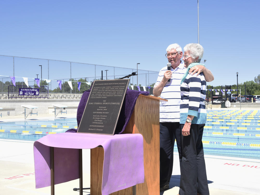 They Tyrrell family at the Aquatics Center behind a plaque