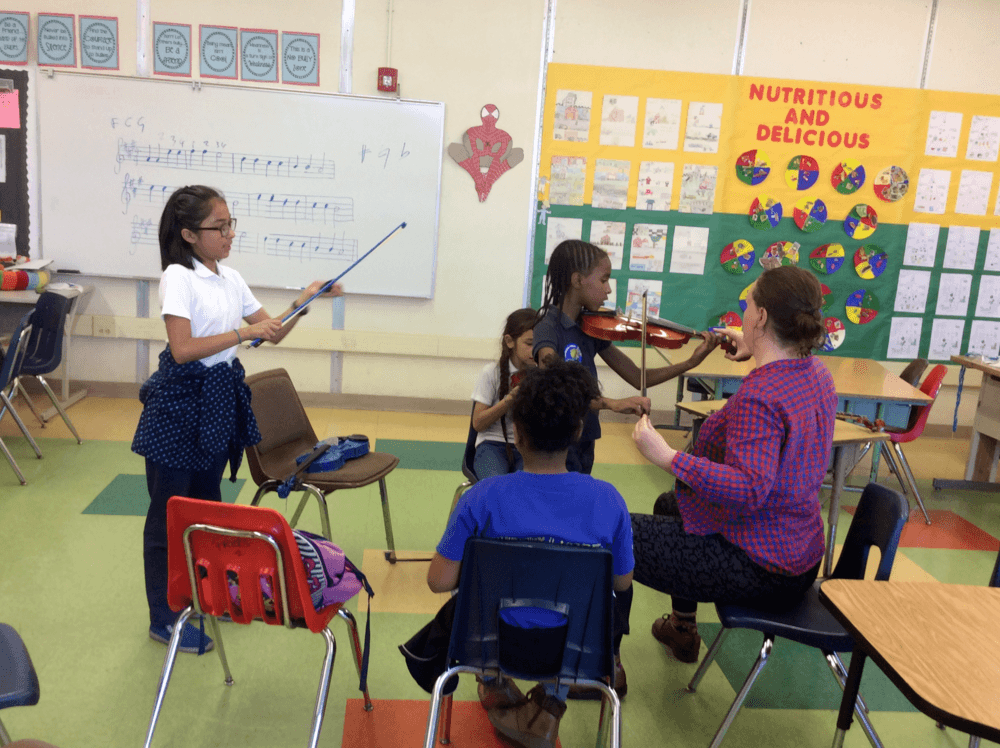 ASES Students learning how to play musical instruments