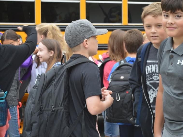 group of boys in front of school bus