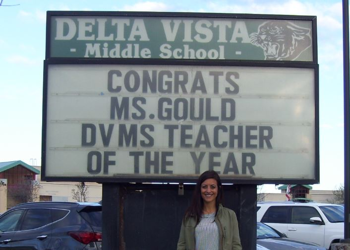 Ms. Gould in front of a billboard sign congratulating her on being DVMS Teacher of the Year