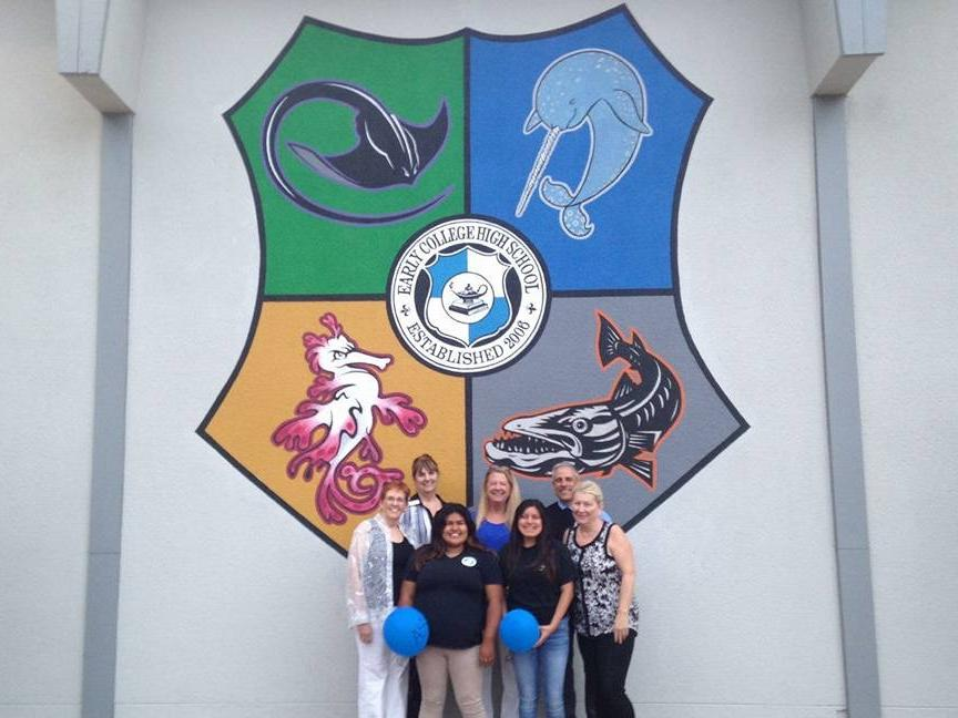 Picture of Four School Board Members, Two ASB Students, and Principal in front  of School Emblem on a Wall