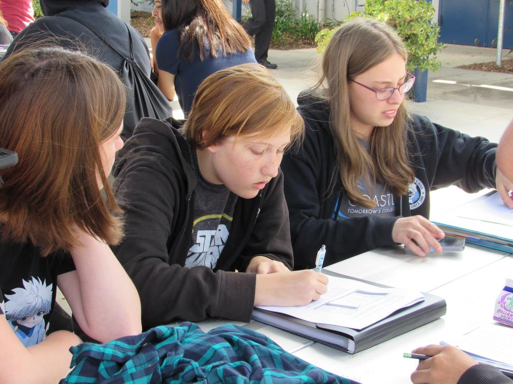 Three Students Working at Table