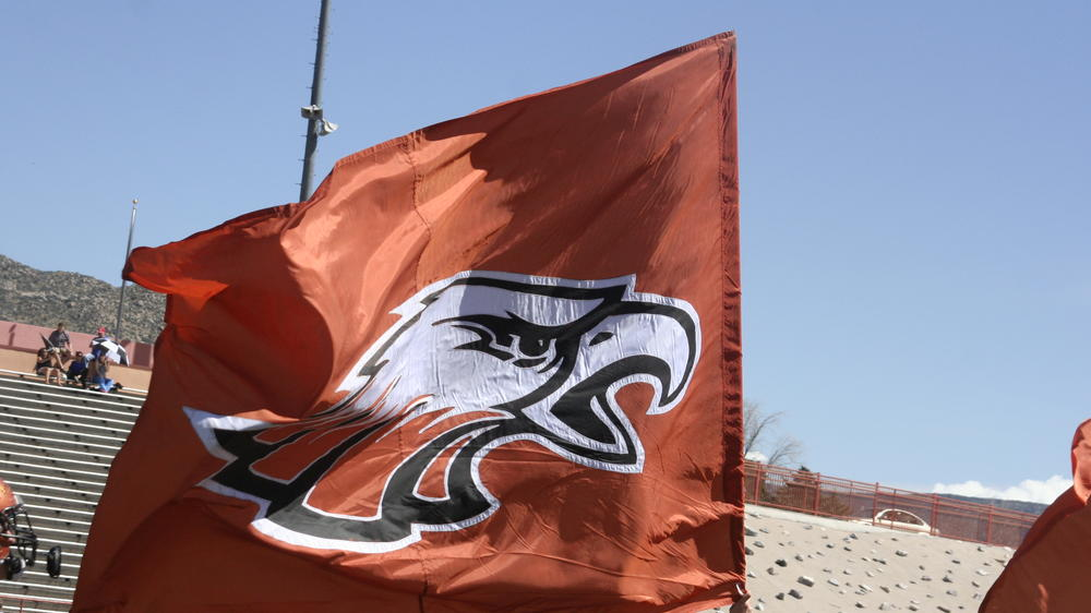 Spirit flag waves in the wind before an athletic showdown.