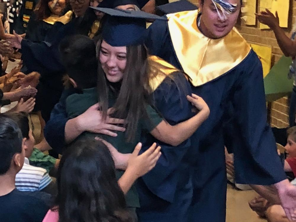 Grads are welcomed with hugs from 3rd graders