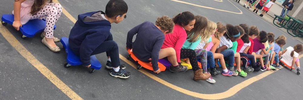 kids on scooter boards making a caterpillar