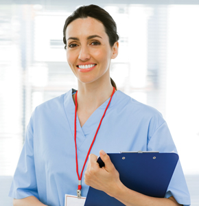 Smiling woman in scrubs holding a clipboard