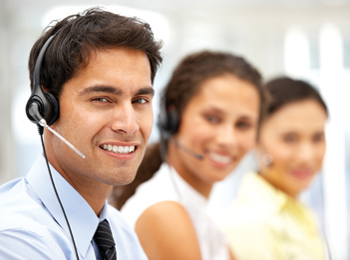 Smiling office staff wearing telephone headsets