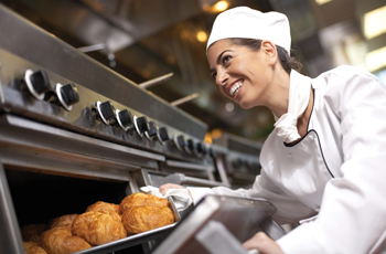 Smiling culinary student removing baked goods from an oven