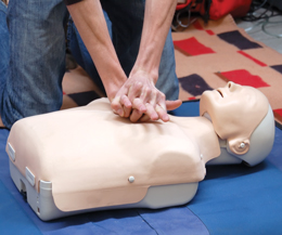 Person performing CPR techniques on a dummy