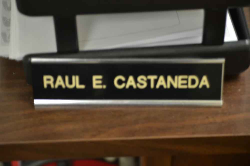 The desk name tag for Raul E. Castaneda