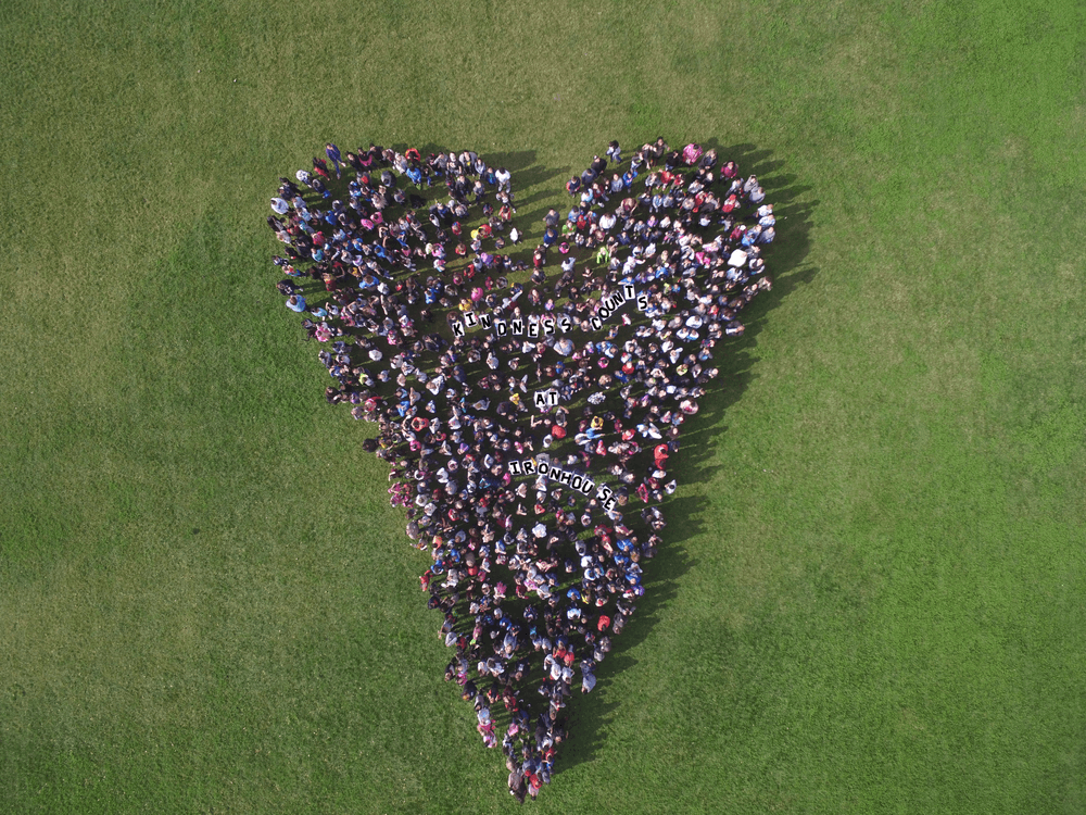 Iron House students standing on the field in shape of a heart.