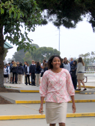 Teacher smiling with students in background