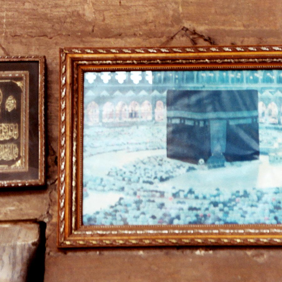 In a mosque looking at a photo of the Kaaba.