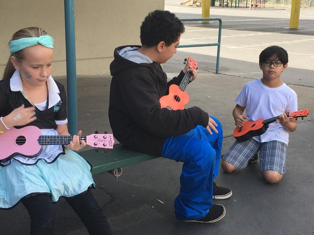 Ukulele practice in music class - Students practice playing songs on the  ukulele in music class on Halloween day