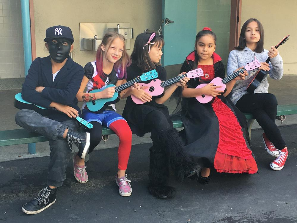Ukulele practice in music class- Students practice playing songs on the Ukulele  in music class on Halloween day