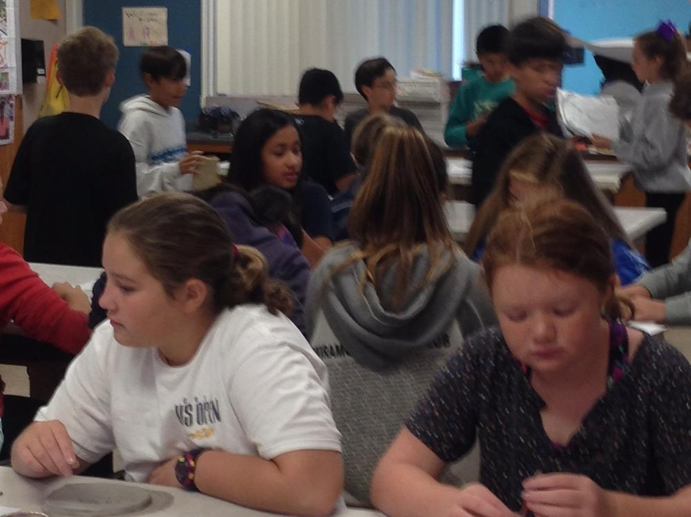 Students practiced pressing wedge shaped designs into clay tablets to write  their names in cuneiform.