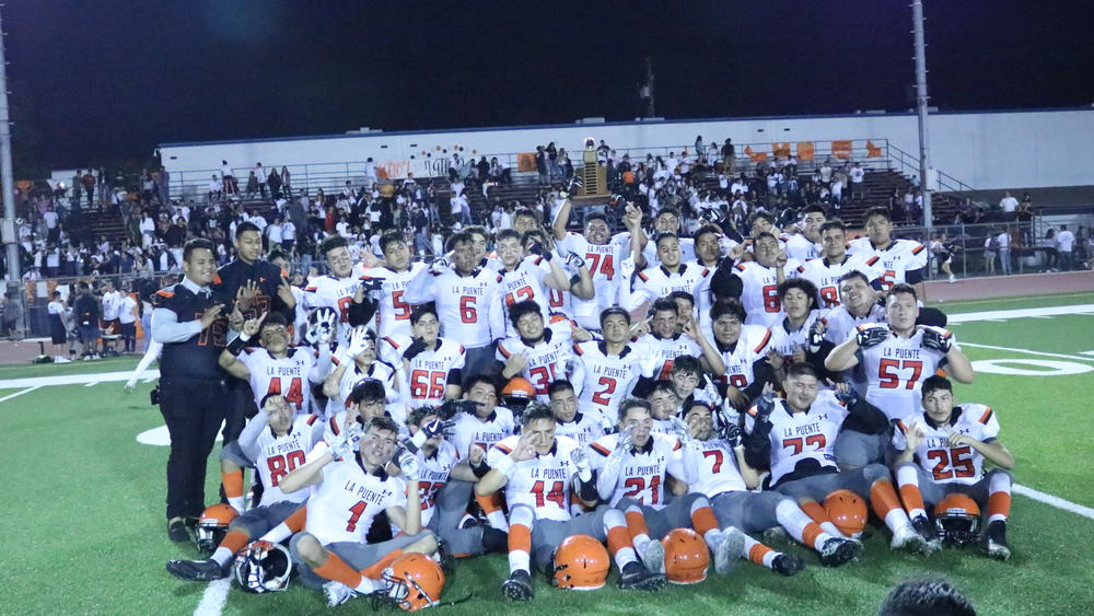 The Warrior Football team gathers to mark their 13th straight victory over the  Workman Lobos.