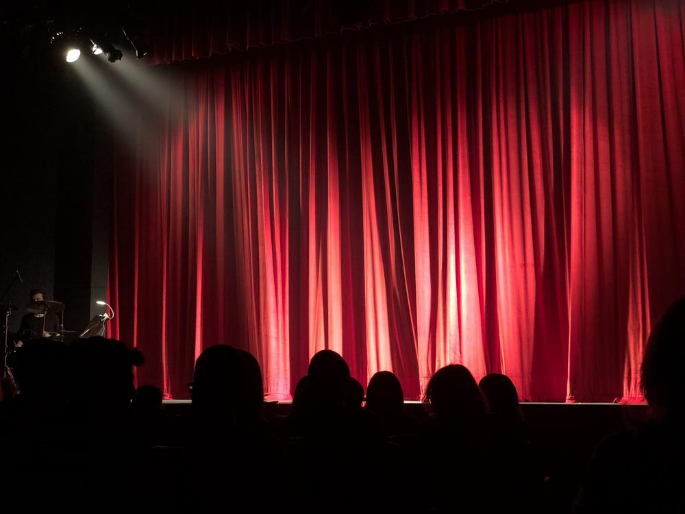Red curtain drawn across a stage