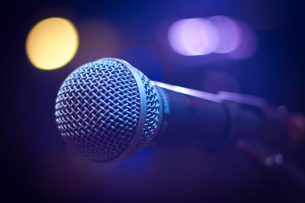 Microphone on stage with lighting in background