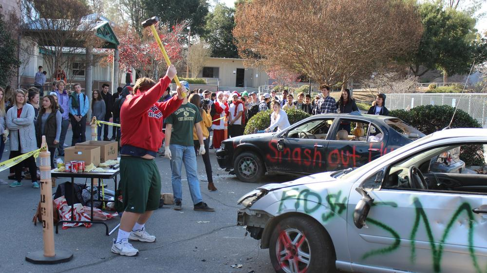 Students smashing cars and collecting cans for can food drive