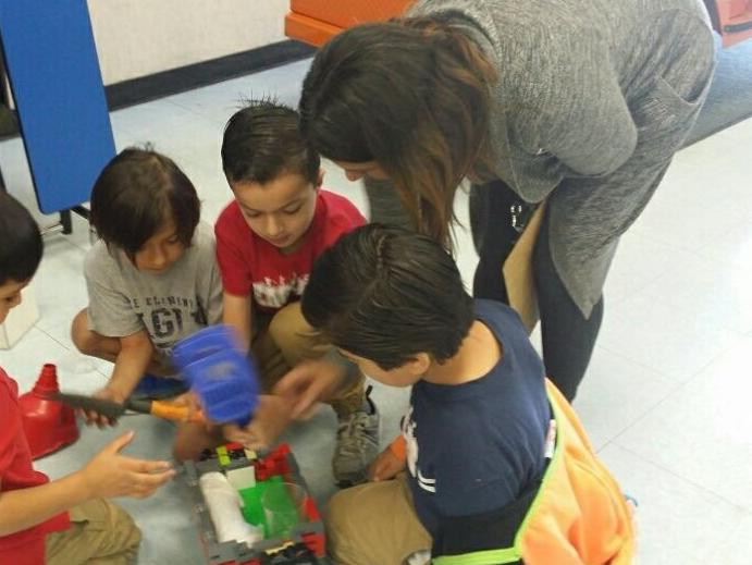 Students working together to fill a lego truck