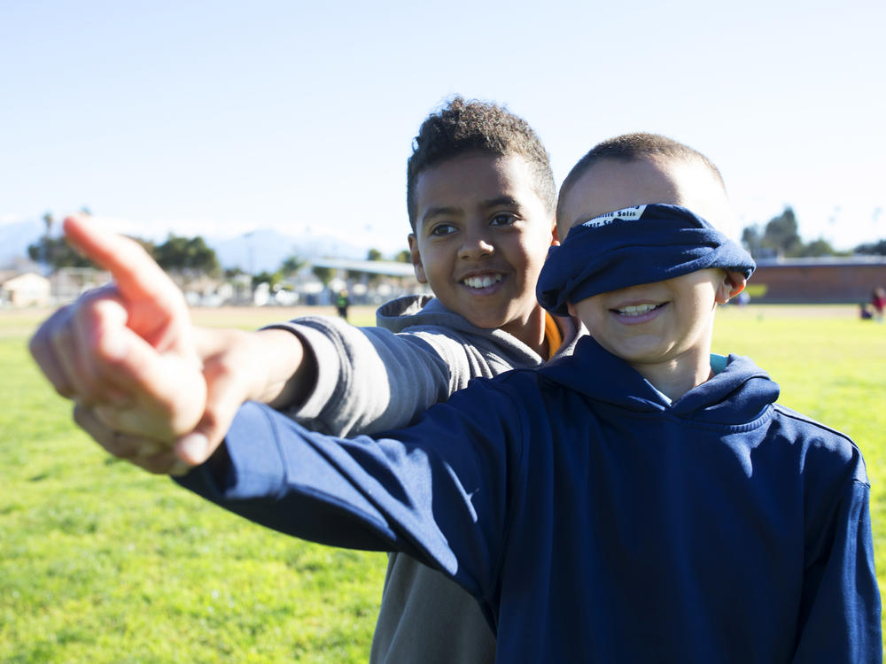Student guiding a blindfolded student in an outside classroom activity