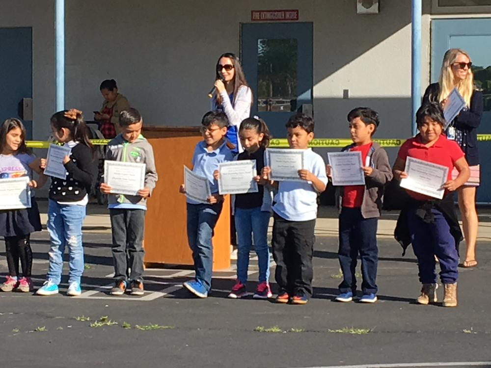 A group of students are receiving an award from the second trimester.