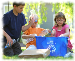Three children placing items in a blue recycling bin