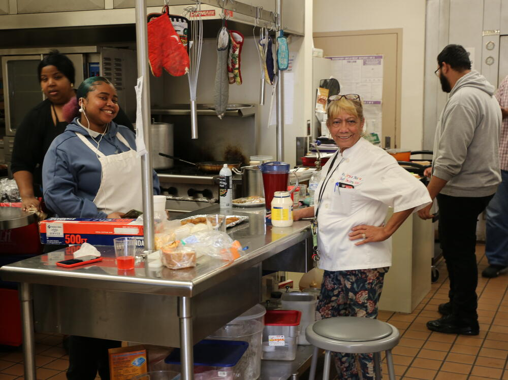 Culinary Arts at YOUAHS with the teacher standing by island counter and  students in school kitchen
