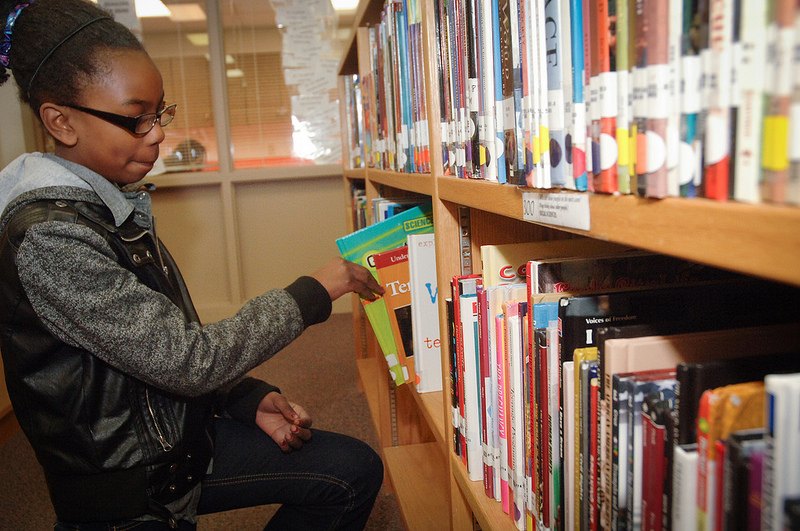 Student selects a book off the shelf in the Library