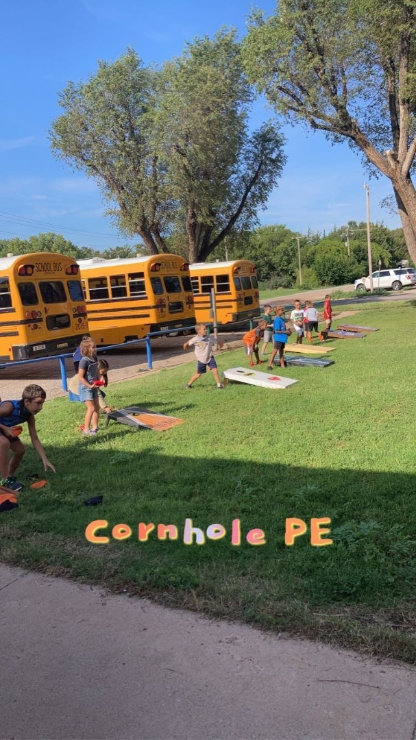 Elementary Students play corn hole.