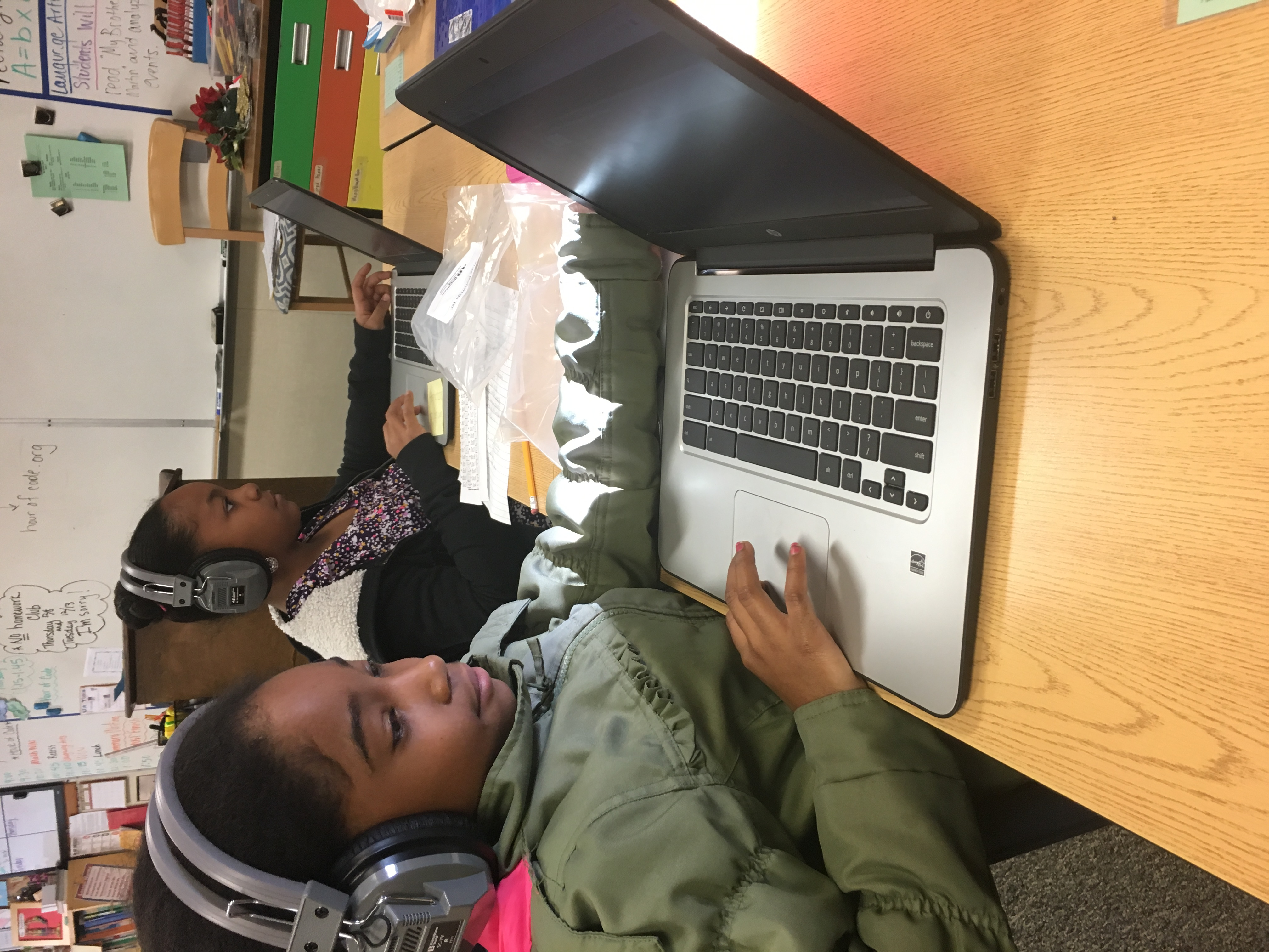 student works on computer with headphones on