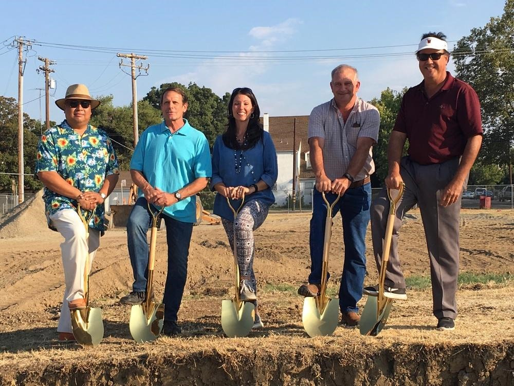 Community Service members standing with shovels at high school ground breaking  ceremony