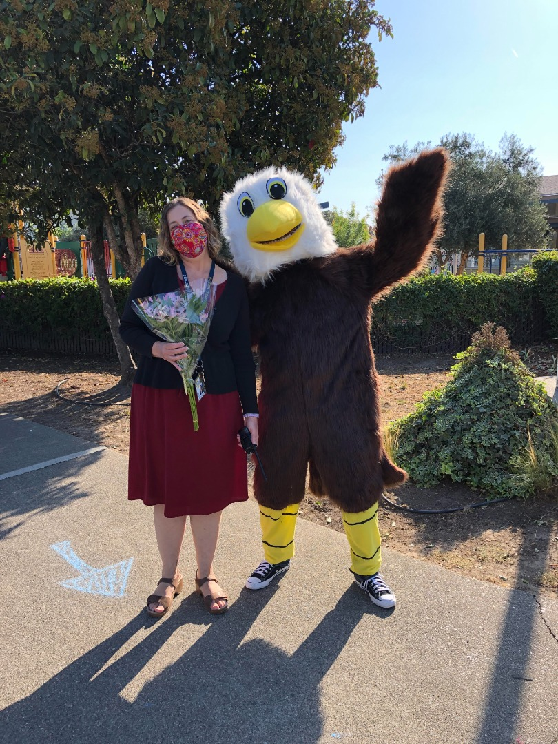 Principal Scott with West Park Eagle mascot standing out front of school