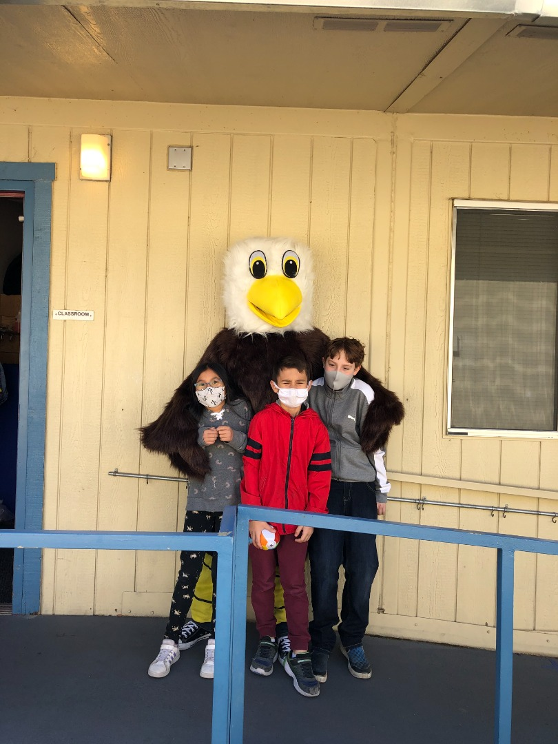Eagle mascot standing outside of classroom with 3 students wearing face masks  during covid