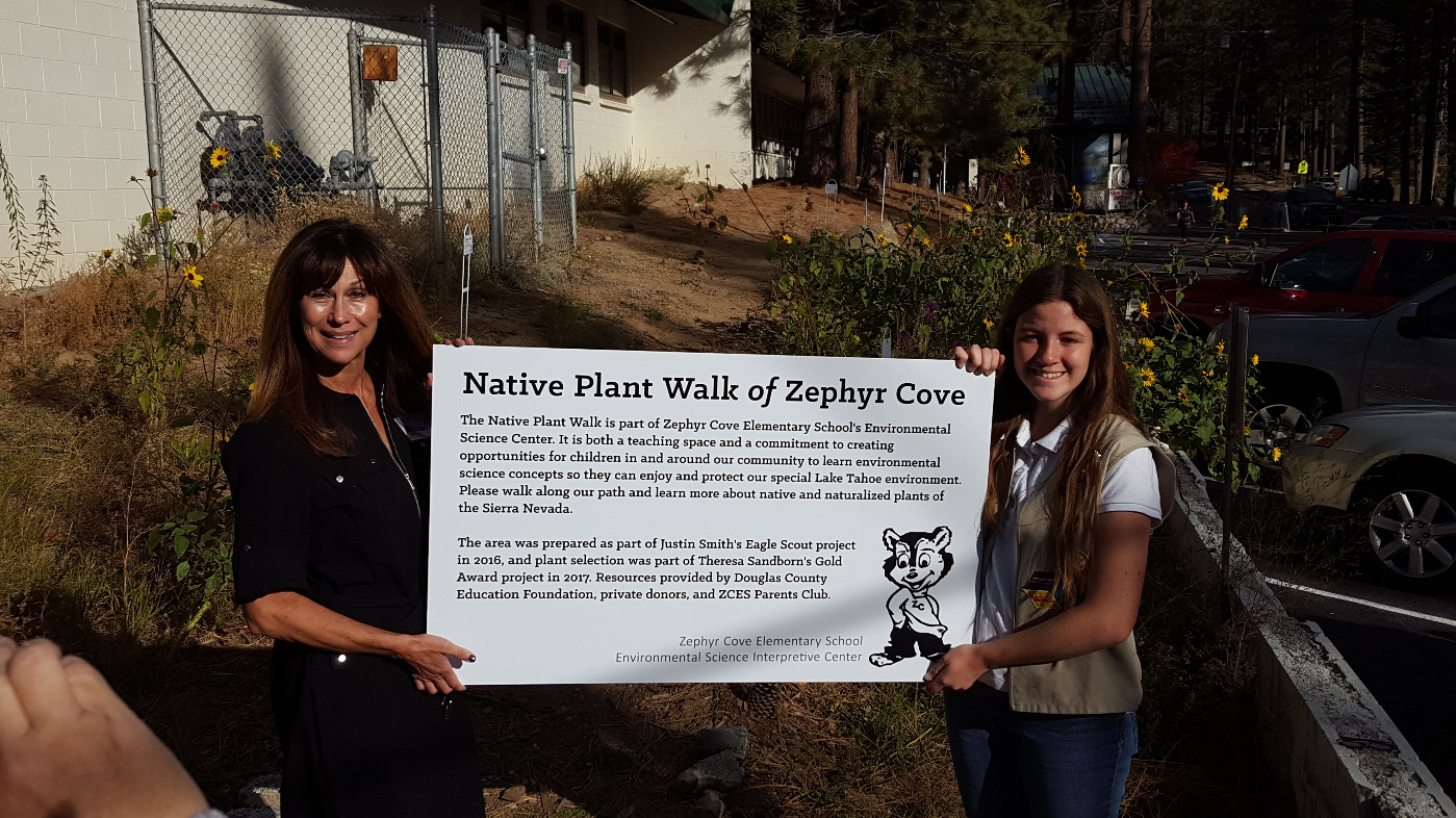 Principal and student holding Native Plant Walk banner