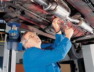 auto mechanic with car on lift working under the car